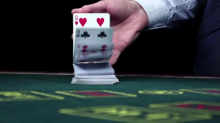 szerencsejáték : Croupie shuffling usual poker cards on table, black, slow motion