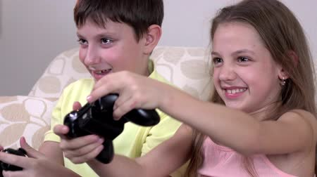 eğlence oyunları : Cheerful brother and sister playing video games in the sofa at home Stok Video