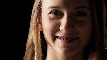 braces : Girl in the shade with braces smiling. Black
