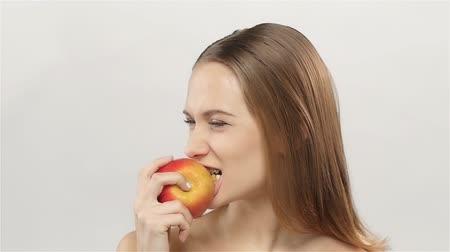 ortodonta : Blonde girl with braces eating apple. White. Closeup. Slow motion