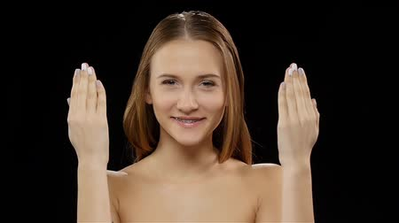 braces on teeth : Girl covers her face with her hands, and then shows his smile with braces. Black. Slow motion Stock Footage
