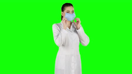 hemşire : Female nurse puts on a blue medical mask. Green screen Stok Video
