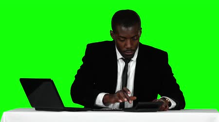 calculator : Businessman uses the calculator and a laptop. Green screen
