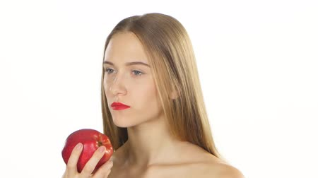 braces smile : Blonde girl with braces eating a big red apple. White. Closeup Stock Footage