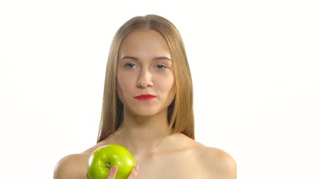 braces : Young blonde model eating a big green apple and smile. White. Closeup
