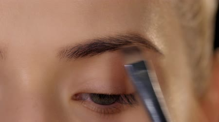 zdůraznit : Beautiful woman draw beauty shape of eyebrows using cosmetic brush. Black. Closeup