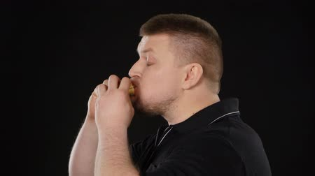 broodje hamburger : Adult man eten hamburger. Zwart Stockvideo