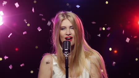 singers : Blonde girl singing into a retro microphone strobe lighting effect Stock Footage