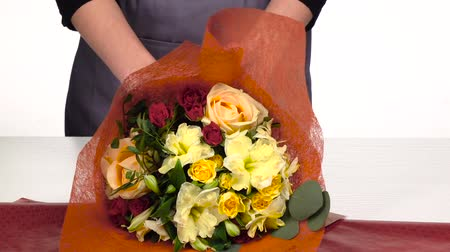 bouquets : Florist does a wrap for bouquet flowers. White. Slow motion. Close up Stock Footage