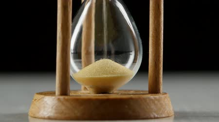 zboże : Bottom portion of an hourglass with a sand. Black. Close up