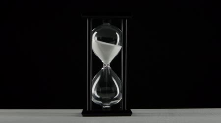 minute hand : Isolated hourglass. Hourglass with white sand. Black