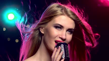 singers : Singer female with retro microphone, long hair developing. Close up. Slow motion