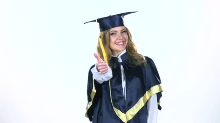 milestone : Graduate showing thumbs up and winking eyes. White. Slow motion