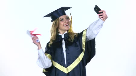 commencement : Female graduate makes selfie photo with diploma. White. Slow motion Stock Footage