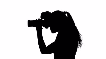 photojournalist : Photographer looks at the camera. White. Silhouette