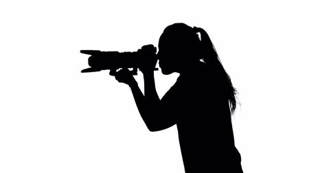 photojournalist : Photographer in studio conducts photography. White. Silhouette
