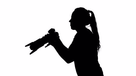 photojournalist : Photographer works in the studio. White. Silhouette