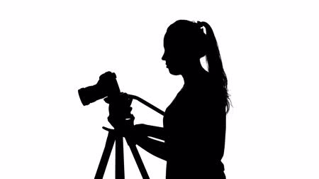photojournalist : Operator adjusts the tripod leg. Photography in studio. White. Silhouette Stock Footage