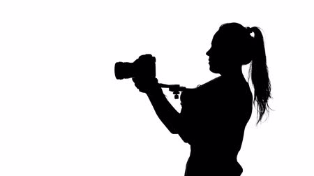 photojournalist : Videographer conducting filming in the studio. White. Silhouette