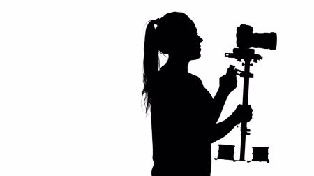 photojournalist : Operator shoots video in the studio. White. Silhouette