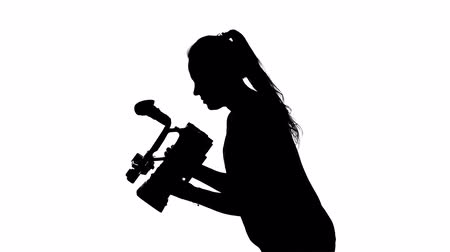 photojournalist : Videographer works with a professional camera. White. Silhouette