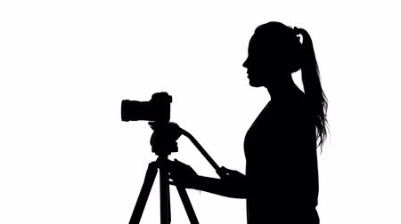 photojournalist : Photographer puts the camera on a tripod. White. Silhouette