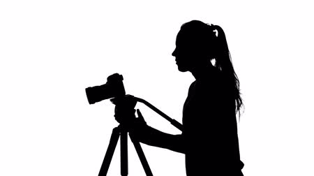 photojournalist : Photographer works with a tripod. White. Silhouette Stock Footage