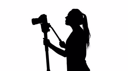 photojournalist : Shooting video or film. Operator at the studio. White. Silhouette