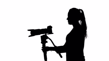 photojournalist : Photographer works with a large lens. White. Silhouette