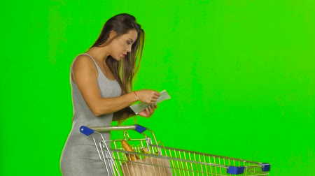 pastry purse : Woman shopping with trolley at supermarket and checking a paper list. Green screen