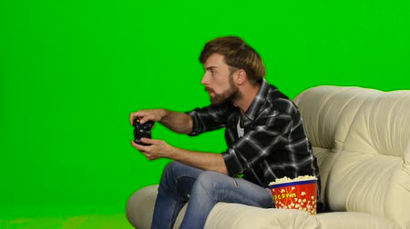 angrily : Man desperately fighting in the game on the console. Green screen