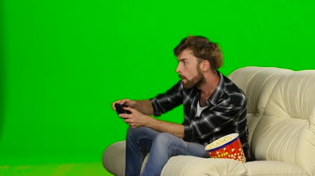 angrily : Man is freaking out and spilled popcorn on the couch. Green screen Stock Footage