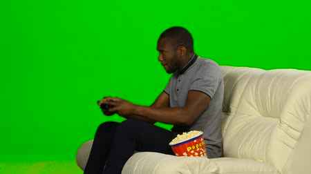 angrily : Man excitedly playing a game on the console and loses. Green screen