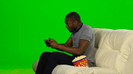 angrily : Man gets the win in the game on the console and dancing. Green screen