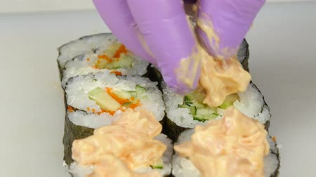 peeled grains : Cook gets sauce on sushi and finalizing. Close up