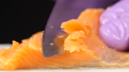 dýka : Sushi chef cuts a slice of trout. Close up