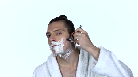 barbear : Male shaves face with blade razor. White background. Slow motion Vídeos