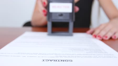 postabélyegző : Girl puts the stamp of the firm on the contract. Close up