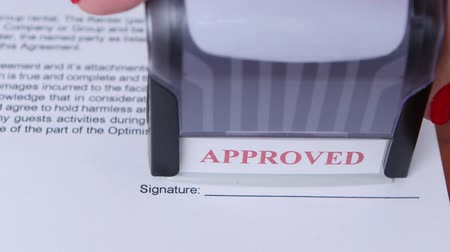postabélyegző : Girl approves a document for collaboration and puts a stamp. Close up Stock mozgókép