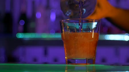 nightcap : Barman mixing cocktail against bar background, shots, slow motion Stock Footage