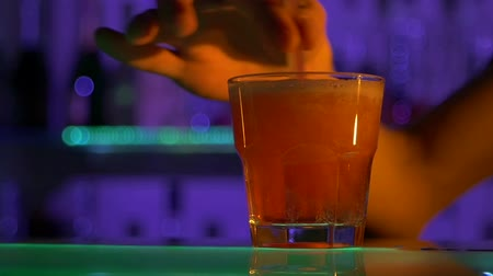 смешивание : Bartender is making cocktail, pouring at bar counter, mixing with  tubules in dark, shots, slow motion, close up
