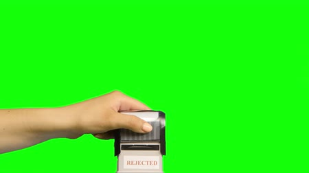postabélyegző : Girl puts a stamp on a green background. Close up. Green screen