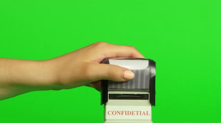 postabélyegző : Stamp CONFIDETIAL on a green background. Close up. Green screen