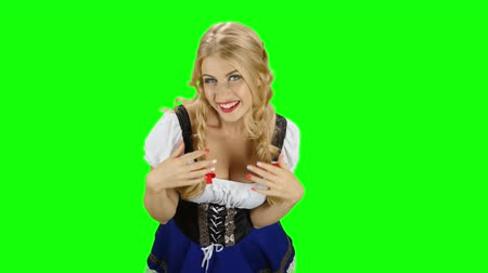 espartilho : Woman in bavarian costume playing with her hair and laughs. Green screen