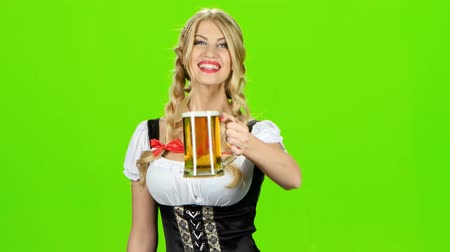 espartilho : Girl in bavarian costume is luring someone for a glass of beer. Green screen