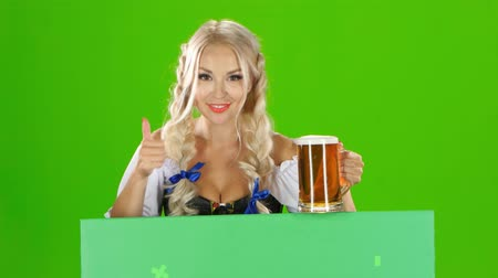 piwo : Bavarian girl looks out from behind a with a glass of beer and showing thumbs up. Green screen Wideo