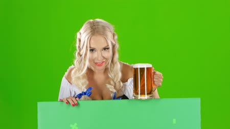 piwo : Bavarian girl looks out from behind a with a glass of beer and winking . Green screen