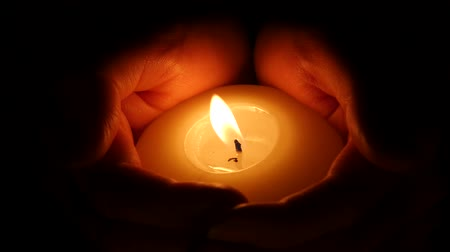 égő : Hands with candle in dark background. Close up