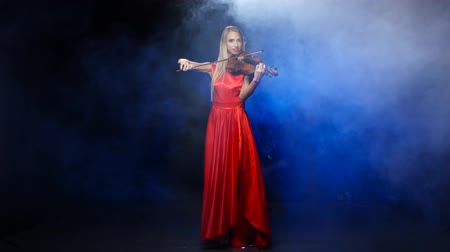 houslista : Girl in a red dress playing the violin. Studio. Smoke