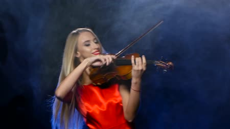 houslista : Woman in a red dress playing the fiddle. Studio. Smoke Dostupné videozáznamy
